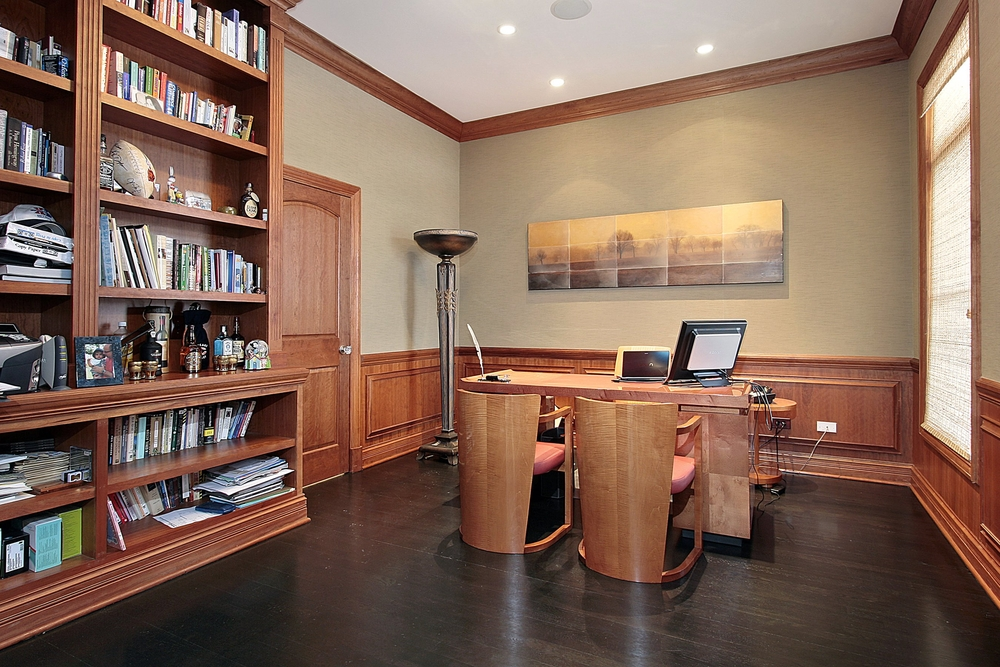 Traditional office space with modern wood office furniture. Wood paneling along lower part of walls as well as minimal wood crown molding along the ceiling