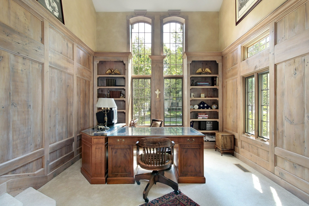 Home office with elevated ceiling, tall arched windows and large antique desk. Wood paneling along walls as well as bookshelves that frame the work space