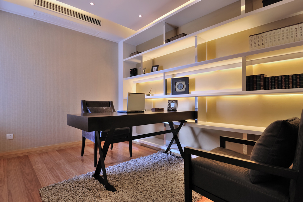 Modern home office with small wood desk, wood floor and bookshelves with back-lighting