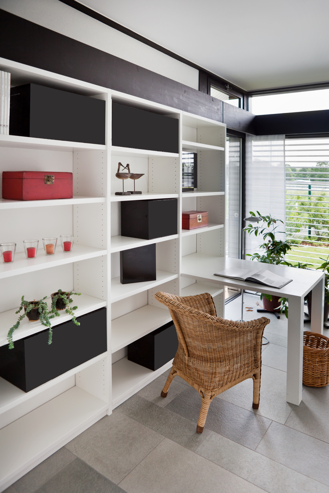 Small home office with desk extending from white bookshelves with wicker desk chair looking out window
