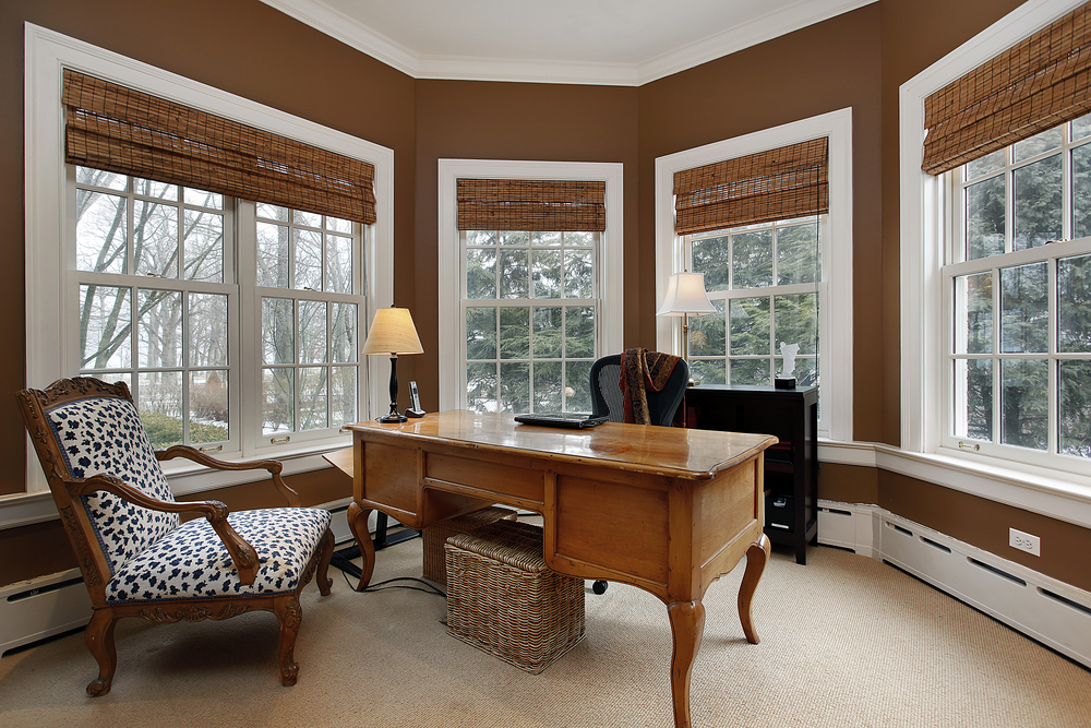 Home office in large semi-circular room with windows