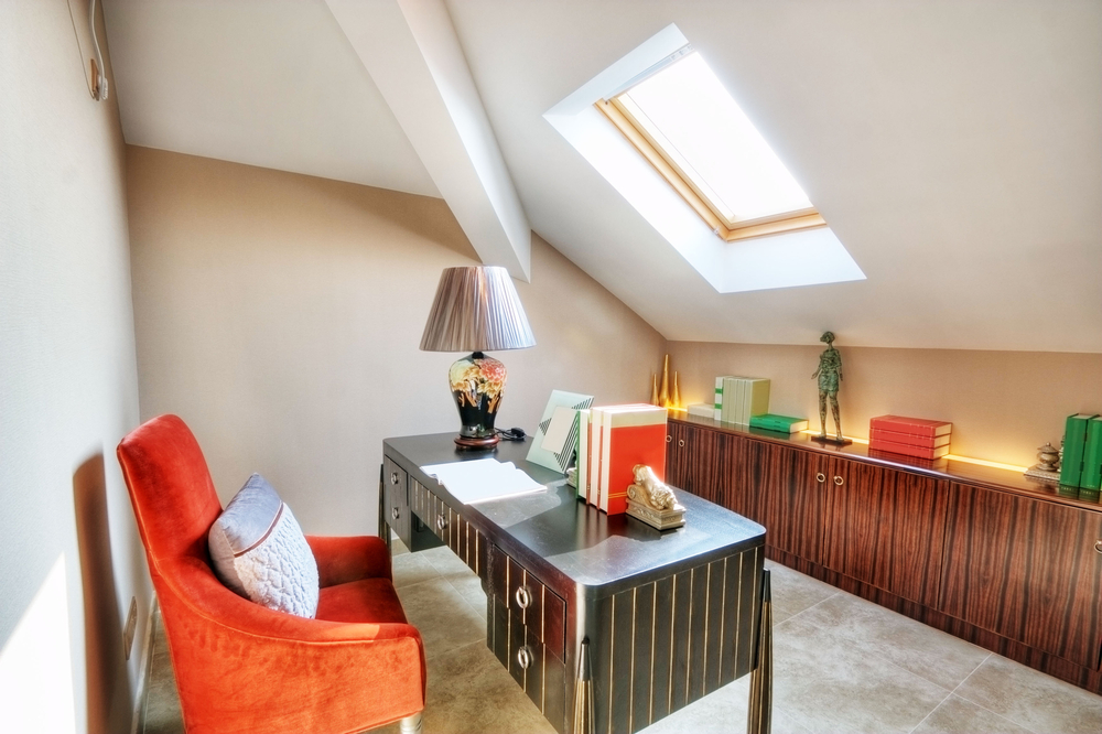 Home office in loft with sloped ceiling and skylight. Small black desk with orange desk chair