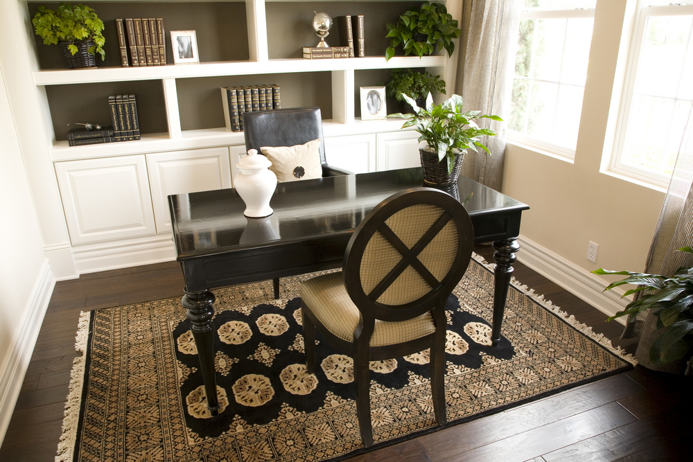 Small contemporary home office design idea with dark wood floor, rug, dark desk and white built-in bookshelves