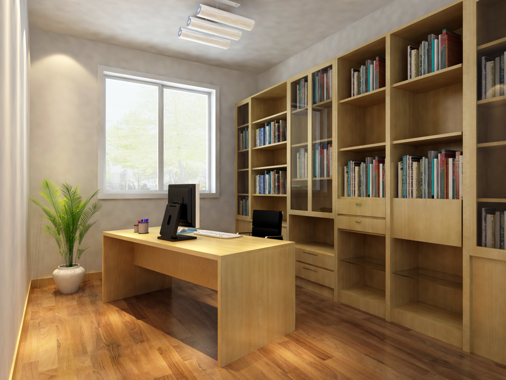 Small home office with wood floor, expansive built-in wood bookshelves and light-wood desk