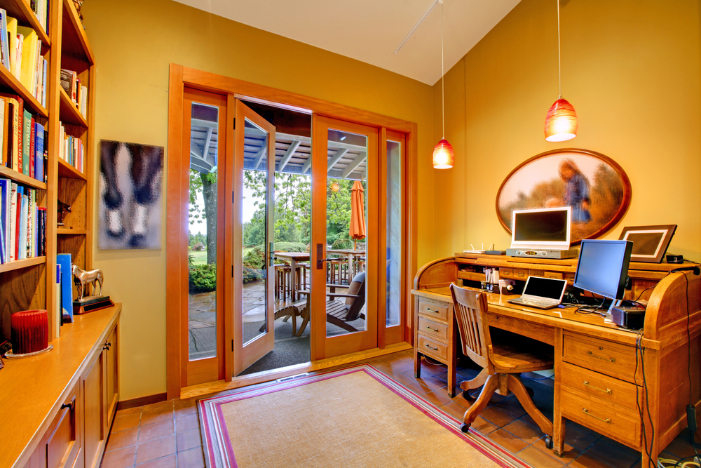 Home office with rolltop desk, wood desk chair, extensive book shelves and double glass doors leading to backyard patio. Color scheme in yellow and white