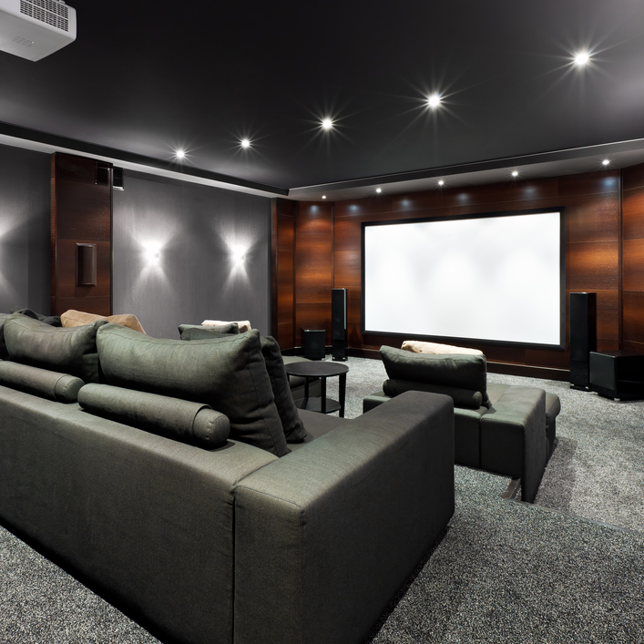 Home theater with stadium seating with sofas in dark grey color scheme and wood panel wall.
