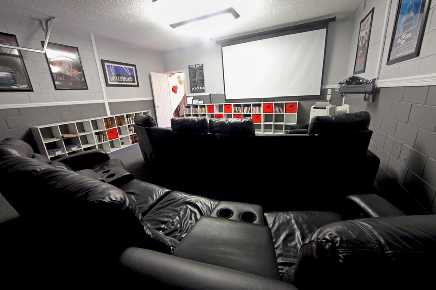 Grey home cinema with projector screen and large black leather theater recliners