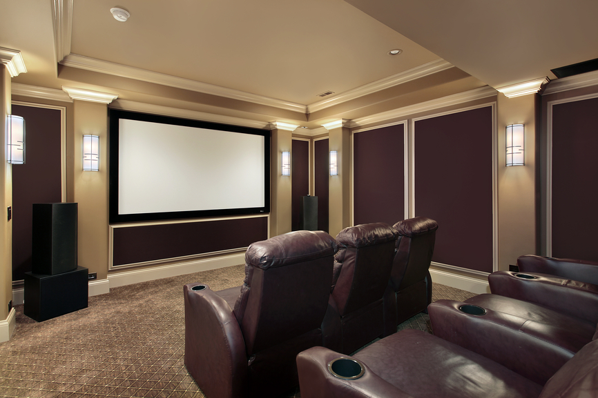 Brown and beige color scheme home theater room with individual leather chairs in stadium seating format