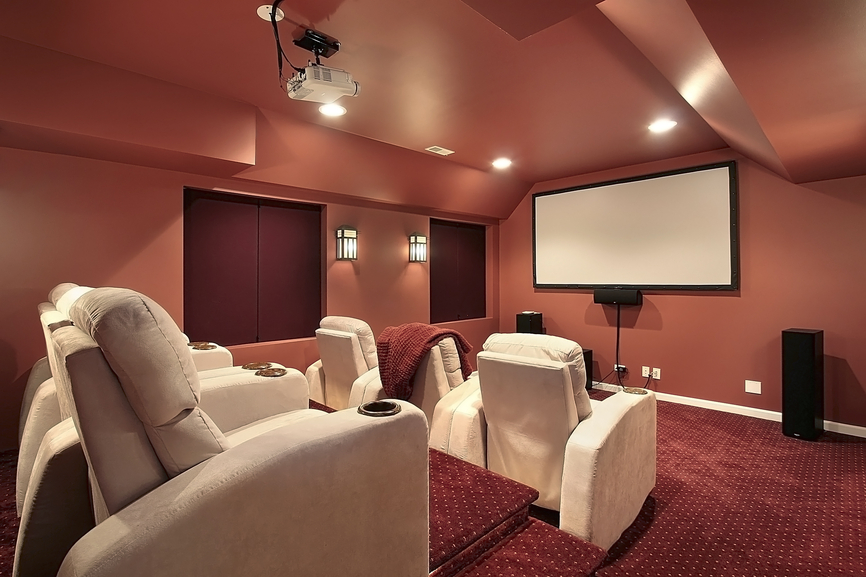 Modern style home theater room with white leather recliners and stadium seating