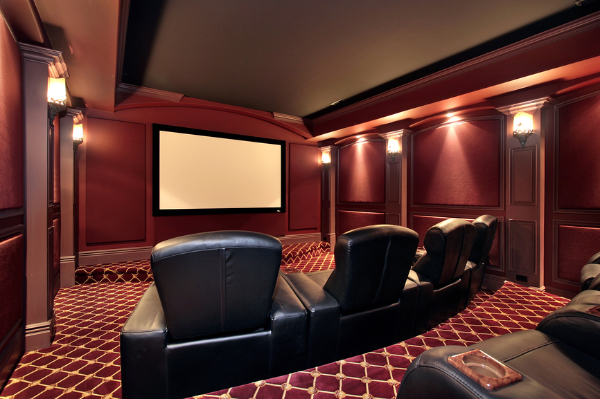 Burgundy color scheme home cinema room with black leather chairs, stadium seating and classical cinema lighting
