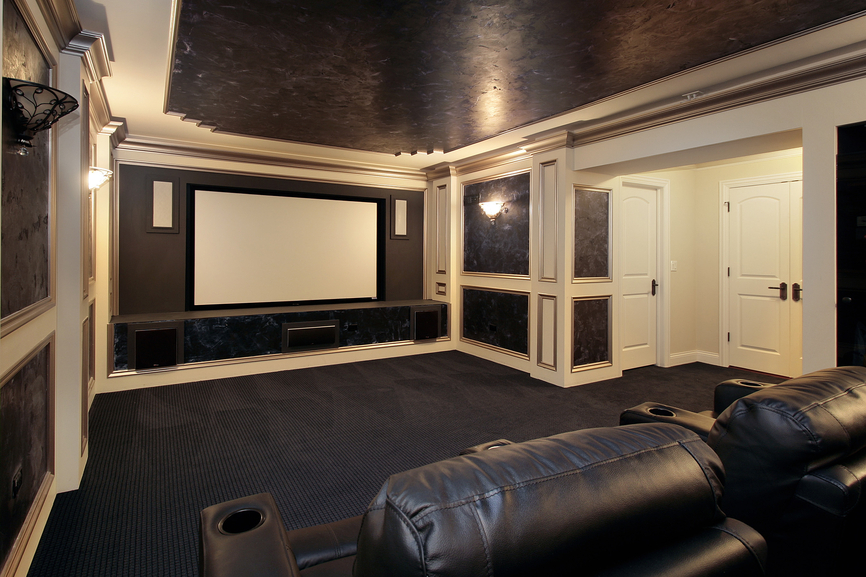 Large brown and black home theater viewing room with white trim and black leather reclining chairs