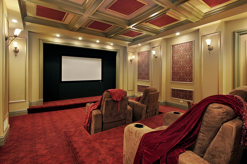 Luxury home theater with rich red carpeting, reclining suede theater chairs and crown molding