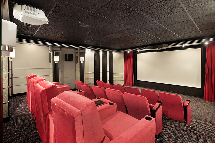 Futuristic home TV theater with dark ceiling, stadium seating and red chairs