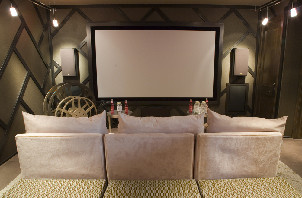 Brown and beige home TV theater room design with seating for 3 people