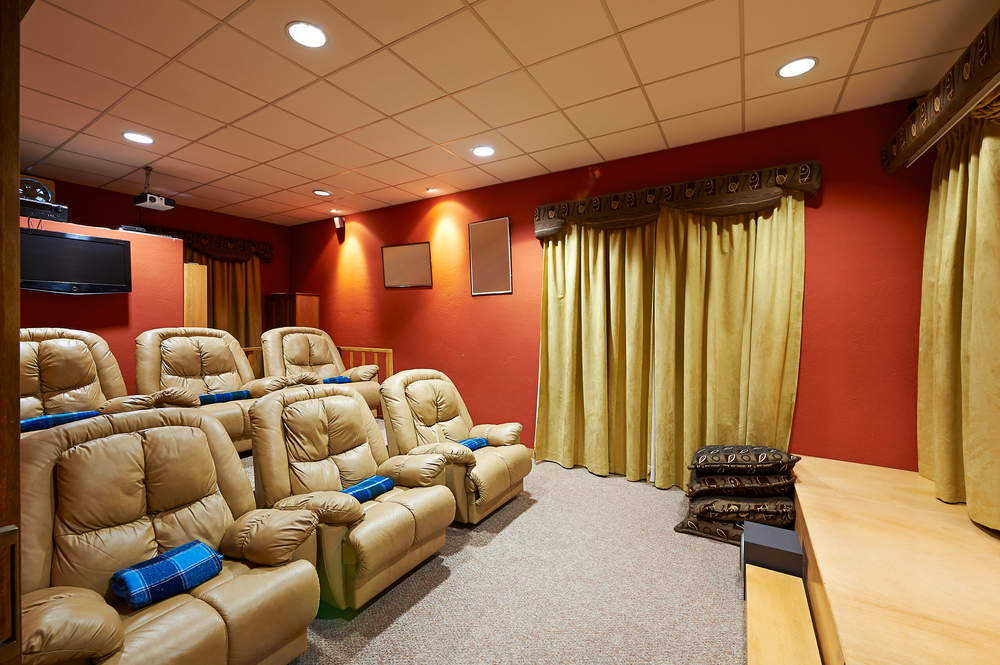 Stadium seating home media room with individual beige leather seats and curtains in front of screen