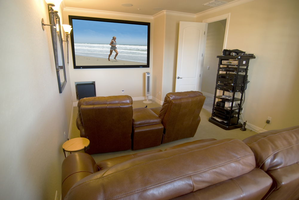 Small room turned into home media room with 4 leather recliners and mounted large flat screen TV on the wall