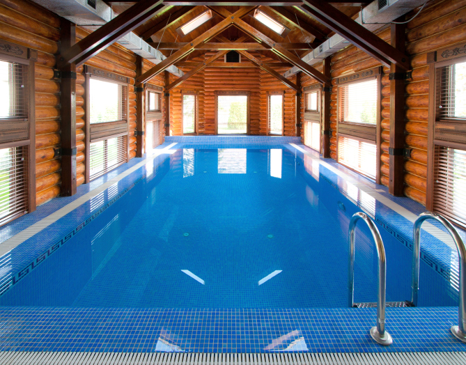 In-ground swimming pool inside large log home