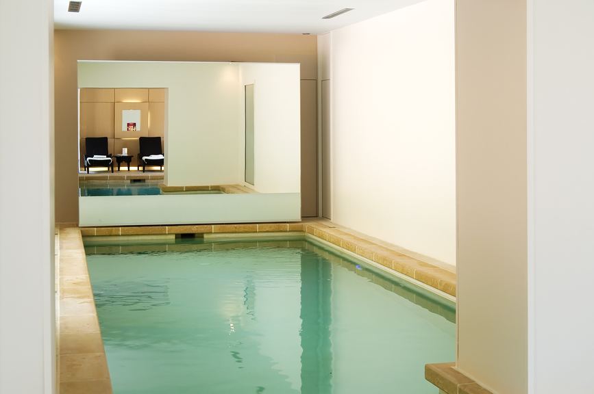 Cozy indoor pool room with white walls and wood décor. Large mirror wall gives the room the appearance of being much larger