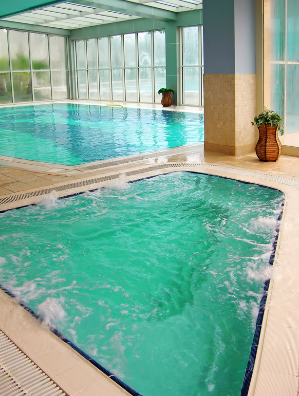 Large indoor pool surrounded by glass with separate hot tub