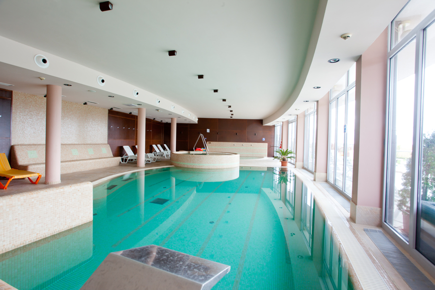 Photo of large indoor lap pool with one wall having floor-to-ceiling windows. Pool has a launch platform for swimming laps.