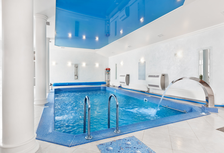 Stylish white and blue indoor pool with fountain