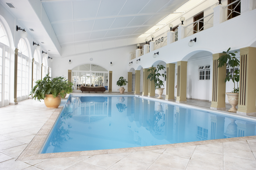 large indoor pool complex with vaulted ceiling exposing 2 stories of the home on one side