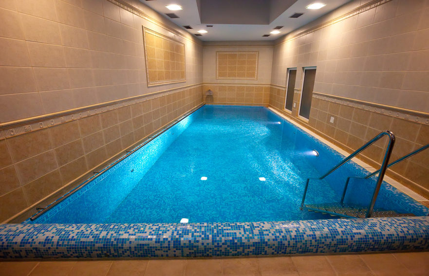 small pool room with rectangle swimming pool surrounded by tiled walls