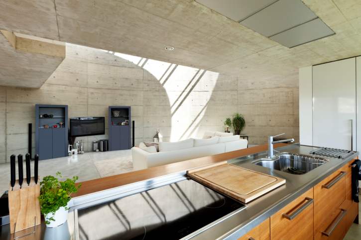 Open concept kitchen with concrete walls and ceiling opening up to concrete living room