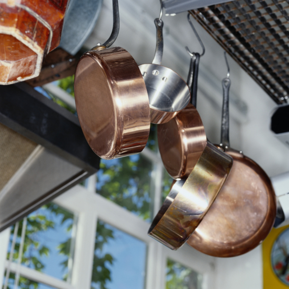 Pot rack with copper pots hanging in kitchen