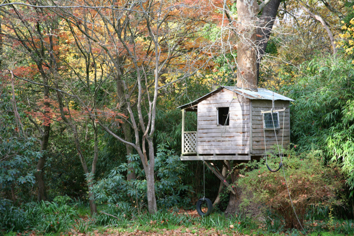 Tree house built around one large tree and stilts. Includes small porch and windows.