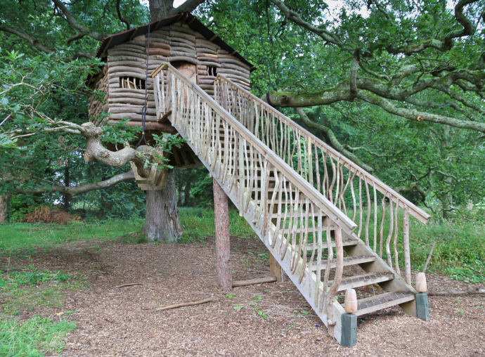 Elaborate log tree house with long stairway leading to front door.