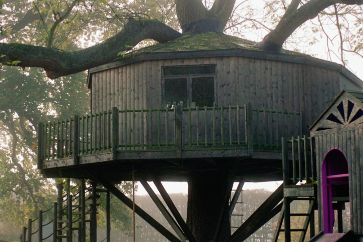 A yurt-style tree house built around one large tree with wrap-around deck.
