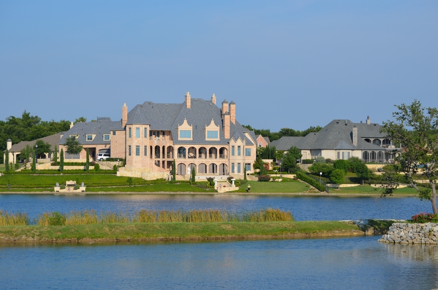 Large red brick mansion with arched columns on a small lake
