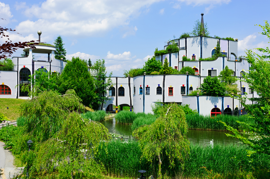 Multi-level rambling white mansion with green roof on the lake