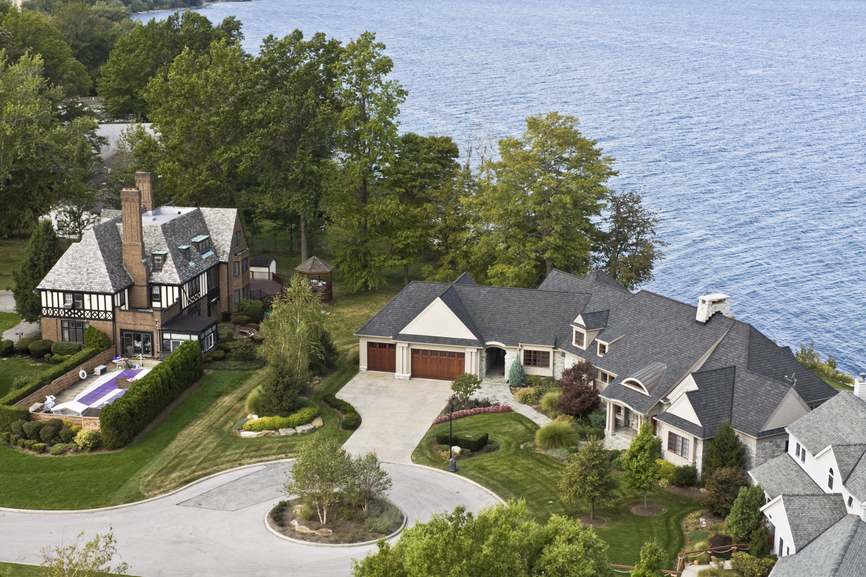 Aerial view of large contemporary home on bluff overlooking a lake