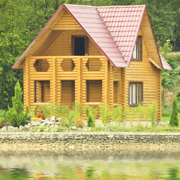 Simple log cabin with red roof on the lake