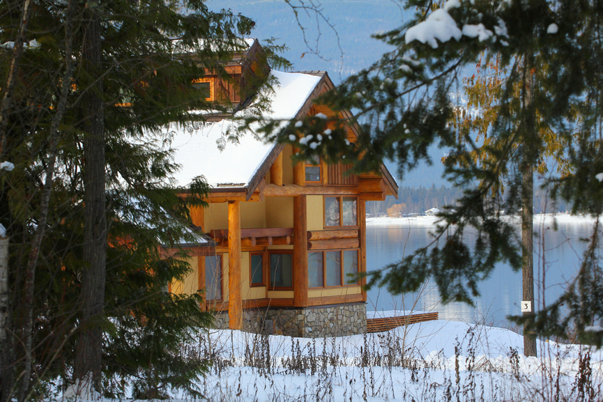 Secluded wood home in the forest on the lake in winter