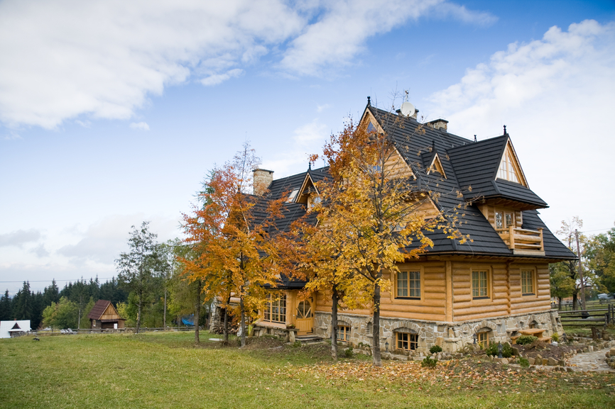 Light colored log home with dark roof on a large grassy property.