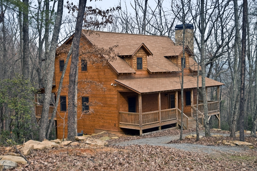 Wood home on the edge of a wooded ravine with porch running full-width of the home.