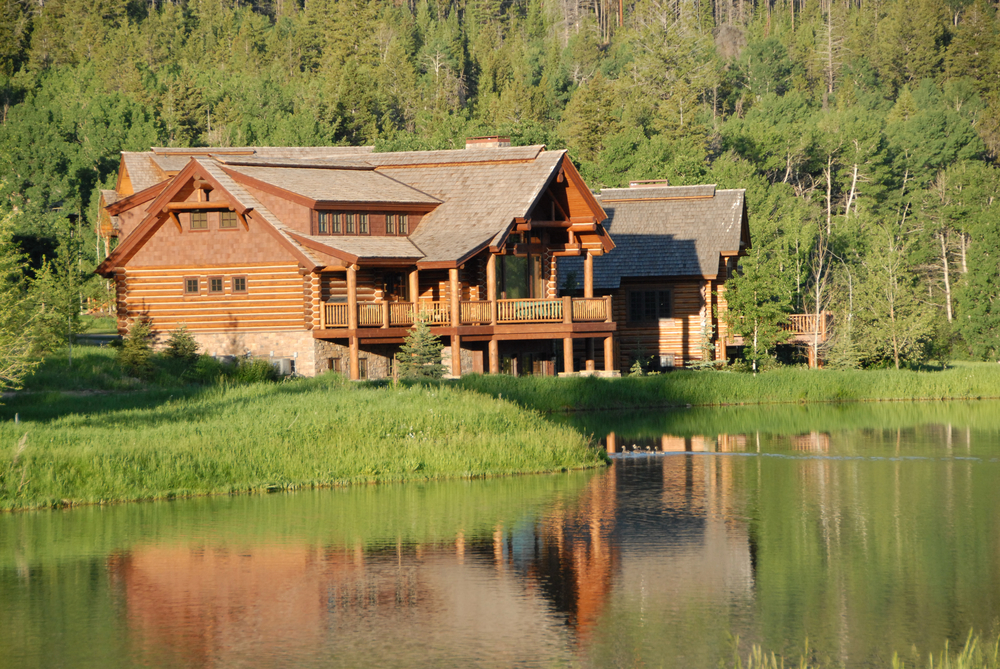 Log home mansion on the lake at the edge of a forested mounted