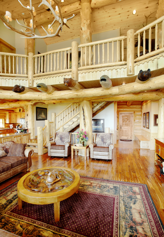 Image of the two-story great room of a log home with view of second-story loft
