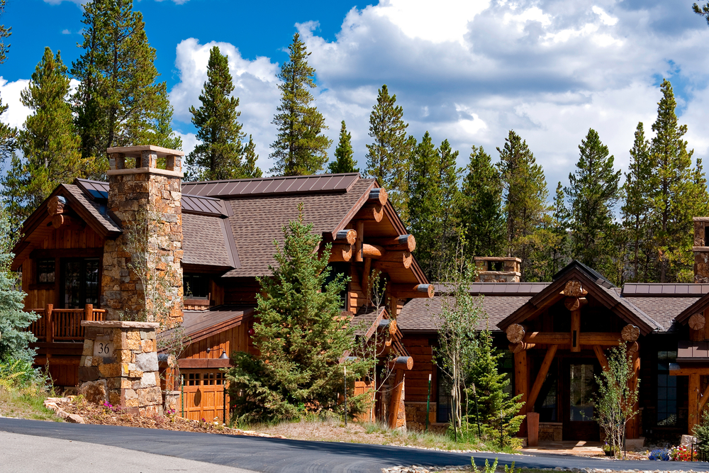 Rambling log home with stone chimney and dark roof with large evergreen forest in the backyard