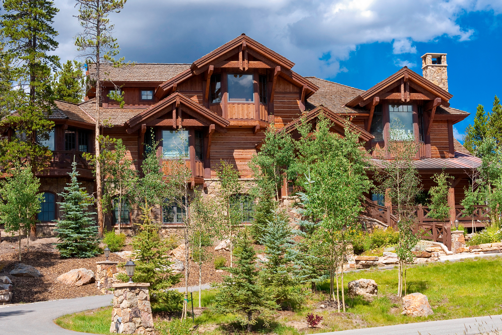 Log home mansion in a ski resort suburb with extensive front-yard landscaping