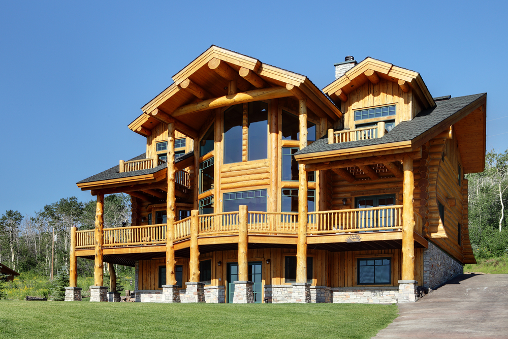 3-story log home with full-width deck on slope of mountain