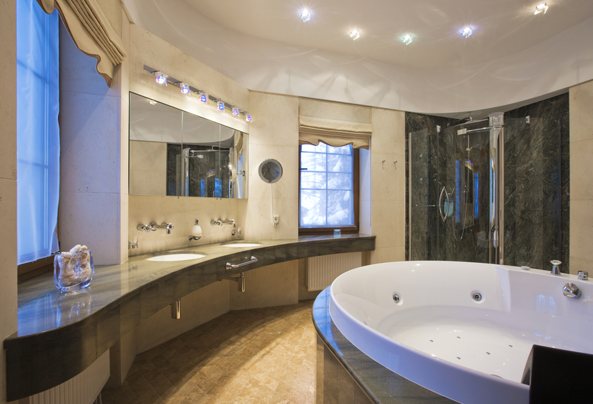 bathroom with long curved wall and counter with large jacuzzi tub