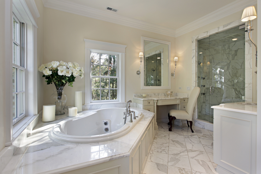 master bath with large step up tub small vanity and dressing area and