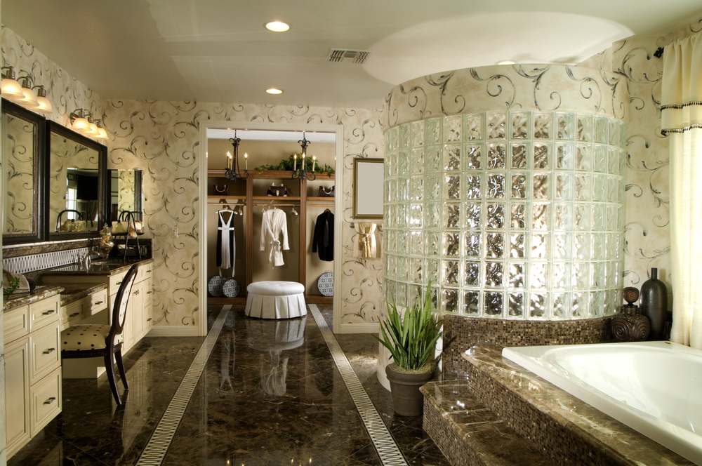 Large luxury bathroom with glass tile shower, marble-enclosed tub and access to walk-in closet