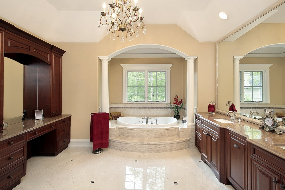 Bathroom in luxury home with bathtub nook and extensive custom dark wood cabinetry