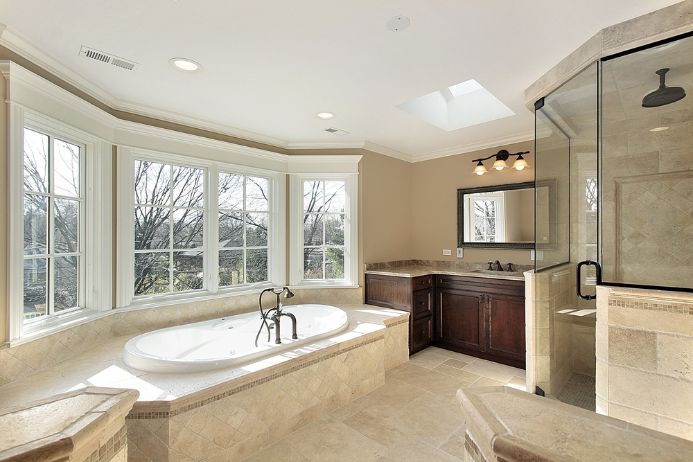 Tub tucked in with bay windows opposite glass shower with dark wood vanity and counter in between