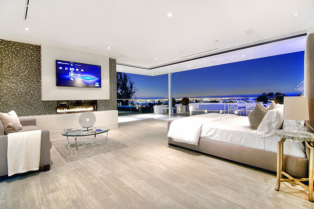 Modern spacious master bedroom design with extensive city views, floor-to-ceiling windows, small sitting area and large screen television mounted above a small gas fireplace